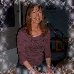 Carolyn Gates, smilingm broadly, behind her drumset.
