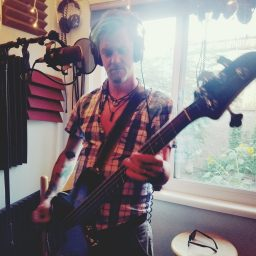 Rory Dowd of Reno band One Ton Dually holding his bass in the studio for the Worst Little Podcast.
