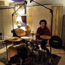 Amar Barboza of Reno metal-core band Salythian posing with his drum kit at Dogwater Studio.