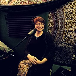 Stephanie smiling and posing for the camera in the studio for Worst Little podcast.