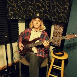 Tell Gresko of Reno metal-core band Salythian holding his bass guitar and posing for the camera.
