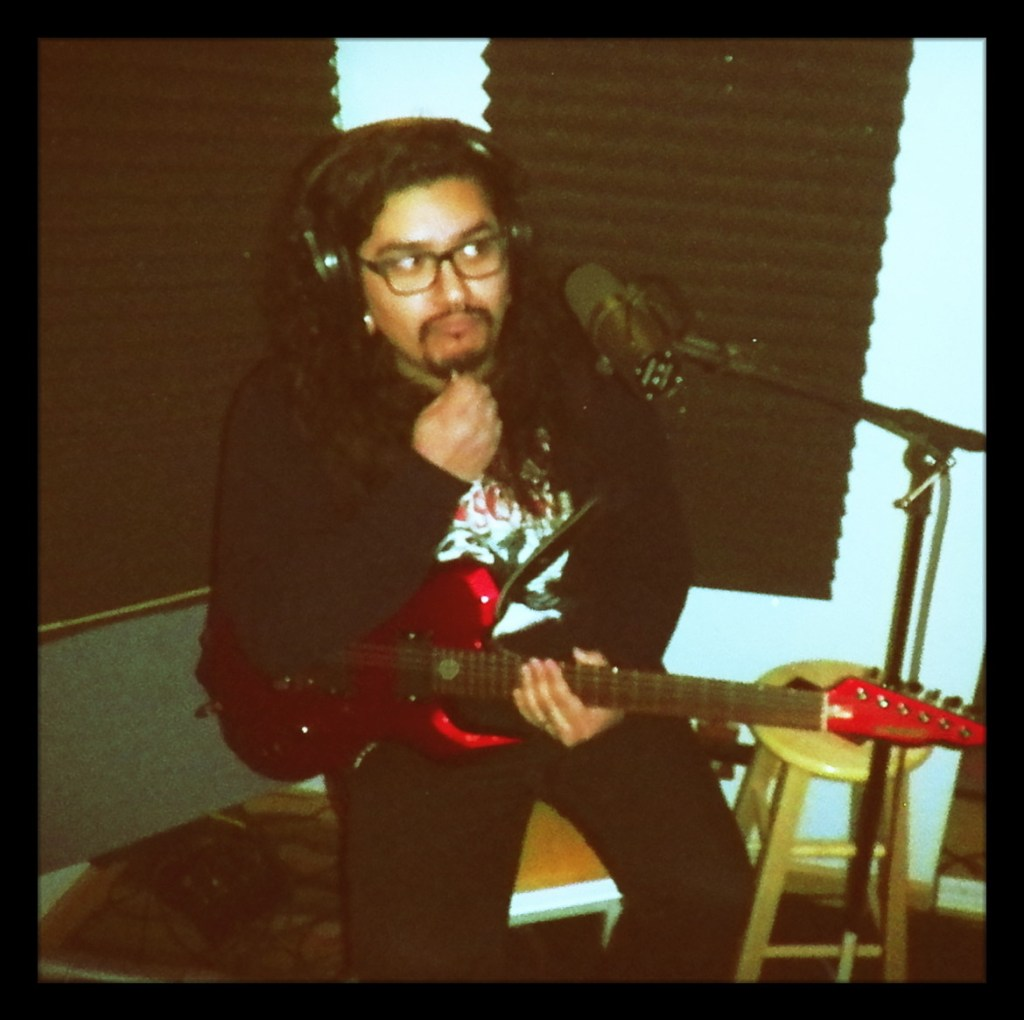 Freddy from Reno band Blacklisted posing thoughtfully with his guitar st Dogwater Studio for the Worst Little Podcast.