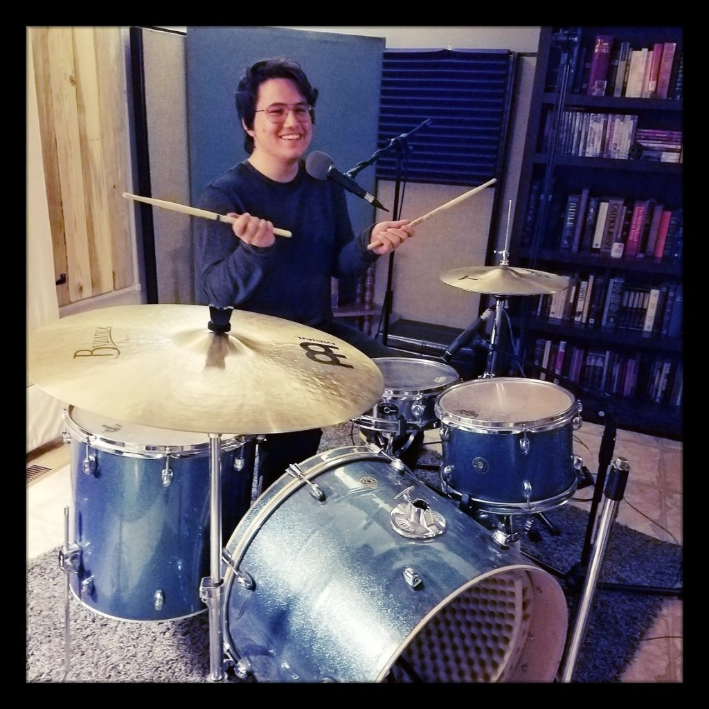 Michael from Reno garage metal band Late For Rent posing with his drum kit at Dogwater Studios recording for the Worst Little Podcast.