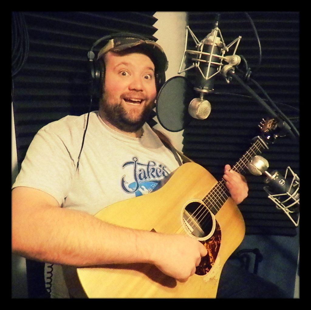 Robbie James of Reno country band Huckleberry Road laughing while holding his guitar at Dogwater Studios.