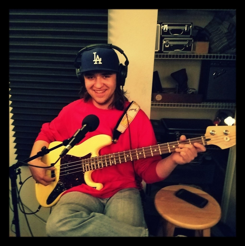Travis from Reno garage metal band Late For Rent holding his bass in the studio recording the Wrost Little Podcast.