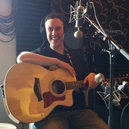 Cole Adams holding a guitar and smiling