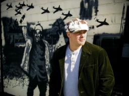 Ryan James poses in front of a mural in Reno.