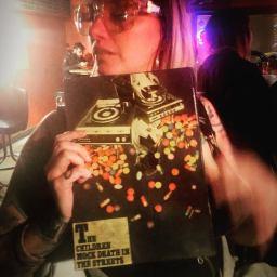 DJ Camz posing with artwork from Jason Kell.