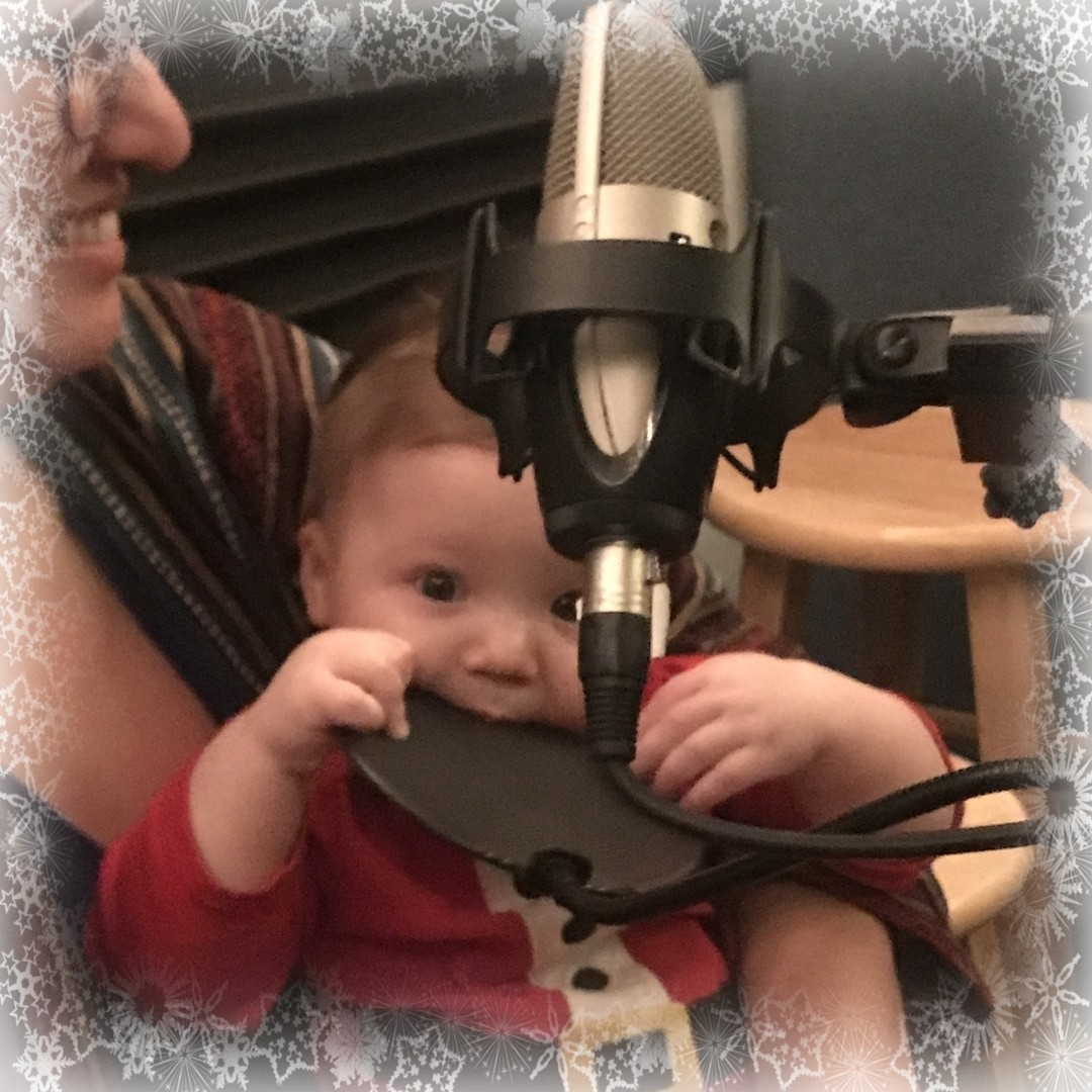 A baby in a Santa outfit tries to eat a pop filter.