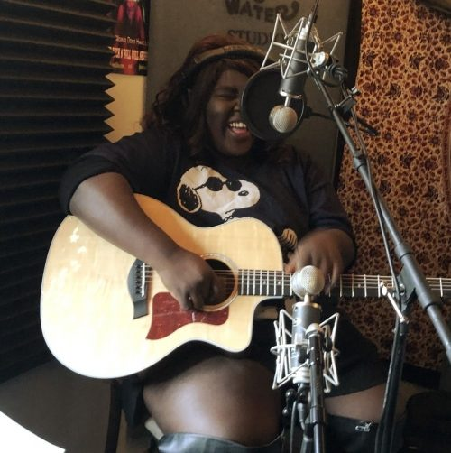 Keva, smiling behind an acoustic guitar