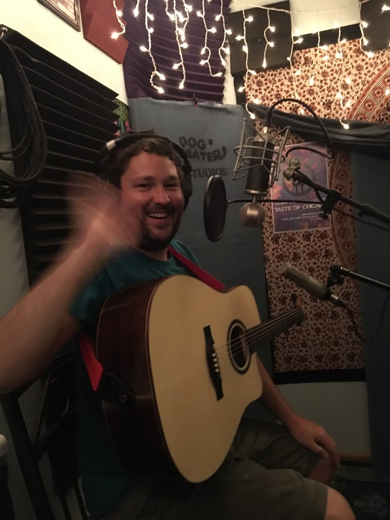 Chris Fox, beardless, smiling and waving while holding a guitar