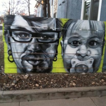 Black and white mural of closeups of Reverend Rory Dowd's face and a baby's face with a pacifier on a lime green fence painted by Joe C. Rock.