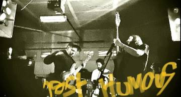 black and white image of the trio Post Humous playing their instruments with the band name scrawled in yellow tagging-style script
