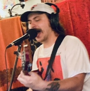 Will Shamberger singing into a microphone while playing guitar.