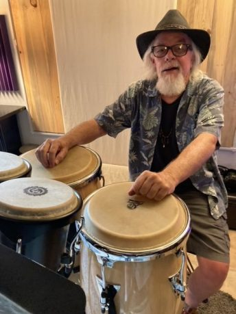Nick McCabe sitting with his congas and other hand drums