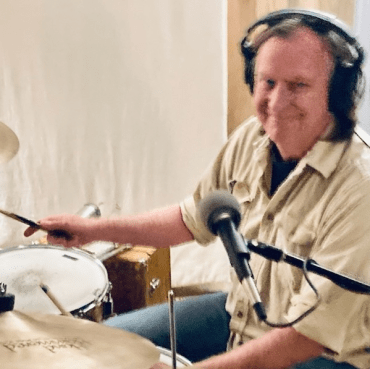 Bill Heise smiling in front of a microphone while playing drums.