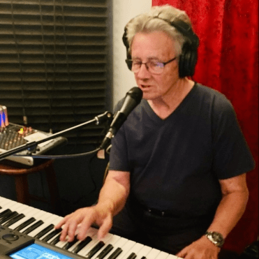Jimmy Vermillion singing into a microphone and playing keyboard.