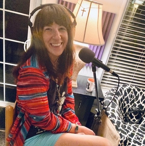 Michelle belle wearing a striped shirt and having fun at the podcast