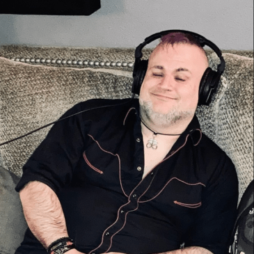 Freddy Freox reclining on a couch wearing headphones and smiling with his eyes closed.