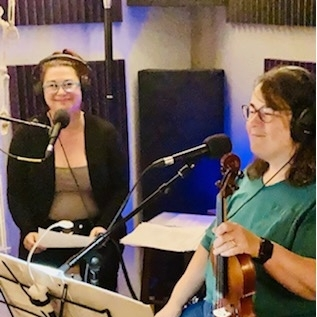 Natalie Laster Jones and Amy Willoughby smiling at microphone
