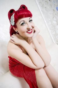 Reno NV photographer and model. Elsie Marie, in a red sparkly dress head on palms, elbows on knees.