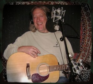 Max Volume with a big grin holding an acoustic guitar while on The Worst Little Podcast at The Dogwater Studios.