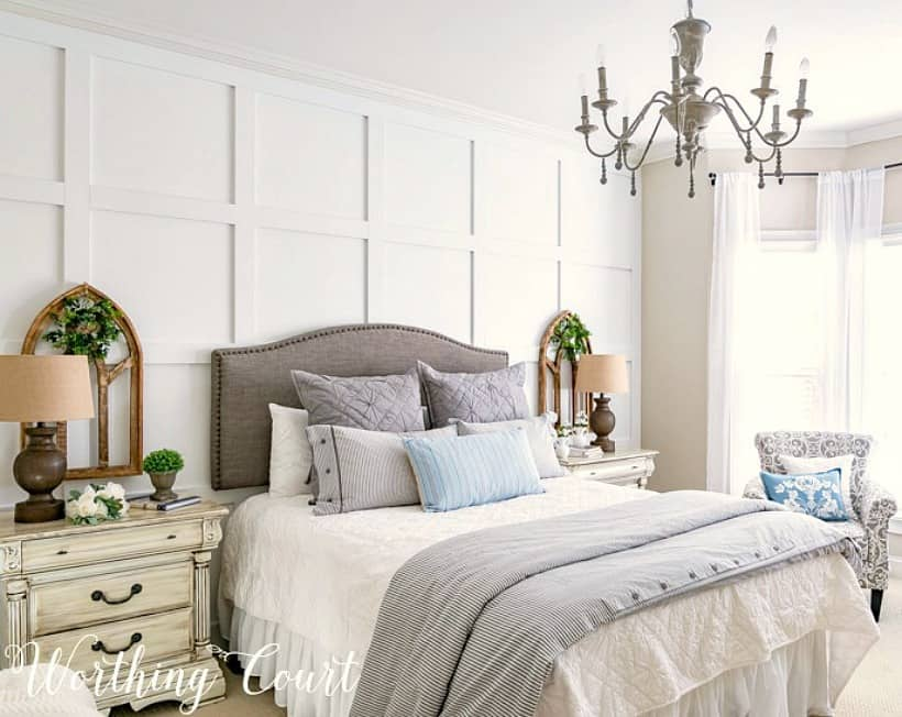 bed with gray headboard against white board and batten wall