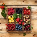 square box with nine 3x3 compartments filled with berries and fruits