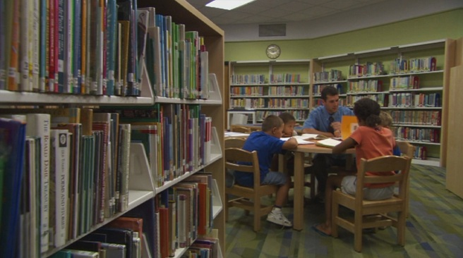 Teacher and students in school library_198097