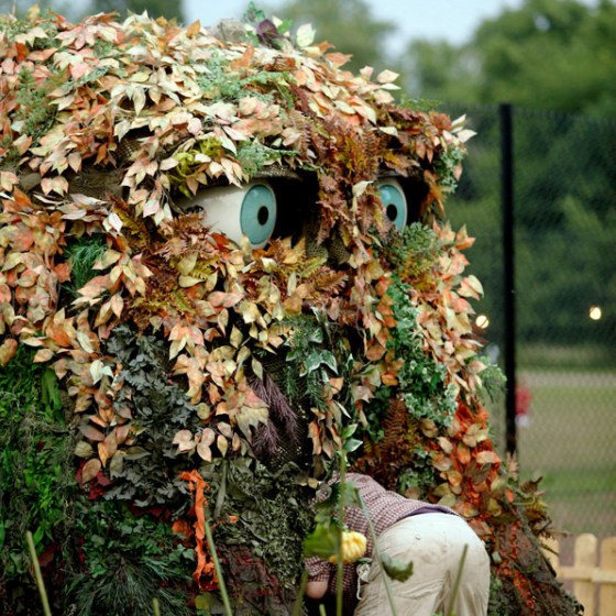Compost heap with eyes, gardener is looking inside