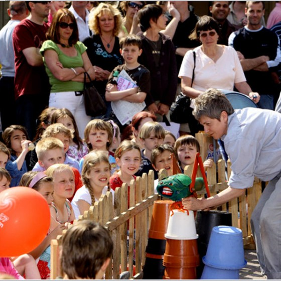 audience watches a grasshopper puppet on a fence