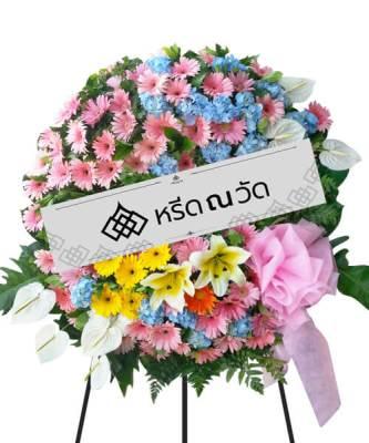 พวงหรีดดอกไม้สด ใช้ดอกไม้โทนสีฟ้า ชมพู เหลือง ตกแต่งด้วยผ้าด้านข้าง