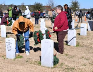 Bryan Correira | Herald Two volunteers remove a wreath from a grave at the Central Texas State Veterans Cemetery on Sunday, Jan. 5, 2014.