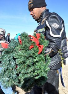Bryan Correira | Herald Sgt. Secoya Allen with the 4th Sustainment Brigade, 13th Sustainment Command, removes a wreath from a grave at the Central Texas State Veterans Cemetery on Sunday, Jan. 5, 2014.