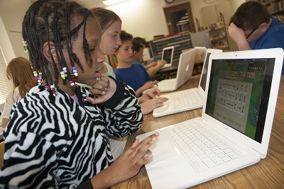 """Fletcher Elementary School fourth graders Nivette Hunter, Sara Randolph and Coleson Barber worked on BrainWare Safari software during the Fletcher Advantage Afterschool Program. The award-winning software helps build 41 cognitive skills in six areas for third through sixth graders: attention, memory, thinking, visual processing, auditory processing and sensory integration in fun games. JPS currently uses BrainWare in fifth and sixth grade classrooms during the school day creating a school to afterschool academic connection.  """"I love playing the game because it helps me think of different ways to get through a maze and solve a problem and it's so much fun,"""" said fourth grader Darius Freeney."""