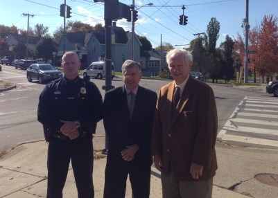 Jamestown police chief Harry Snellings, Jamestown Mayor Sam Teresi, and Johnson Foundation co-trustee John Sellstrom stand at the intersection of Main and Eighth Streets, one of the locations where traffic security cameras were recently installed in Jamestown.