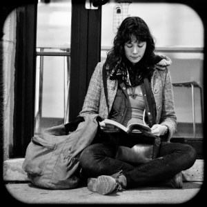 Girl reading at the bus stop.