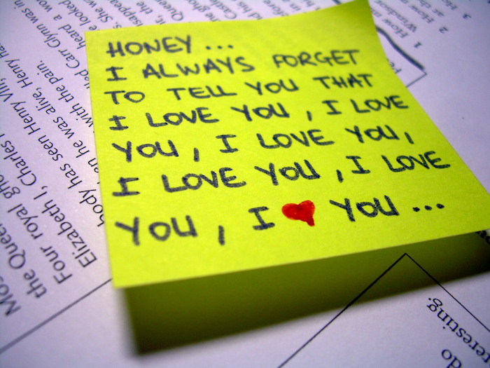 A handwritten love letter on a yellow sticky note.