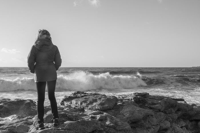 Black and white photo of a woman looking out to sea.