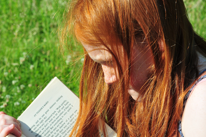 Redheaded girl reading a book.
