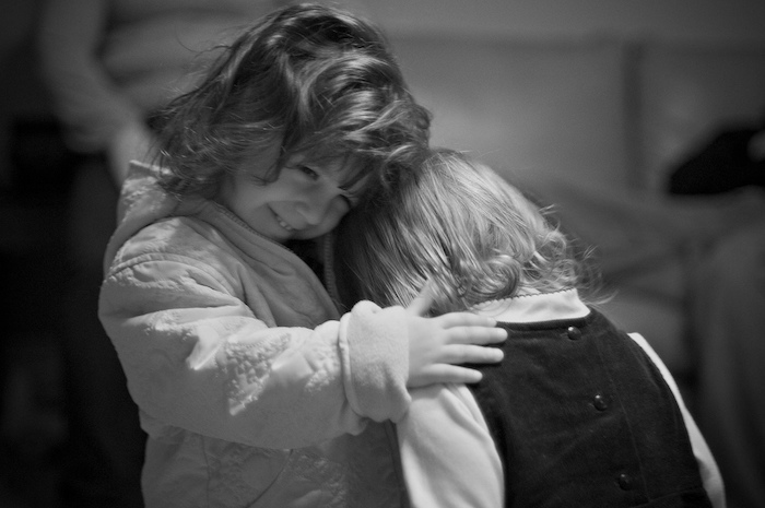 A young boy and girl hugging. Black and white photograph.