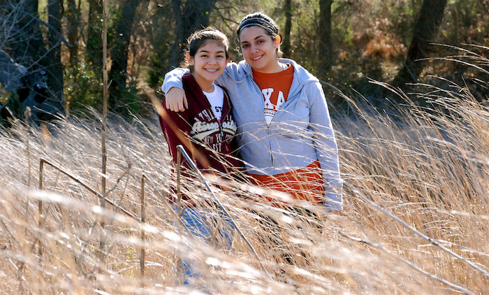 Two friends give a side hug while hiking in Austin, Texas.
