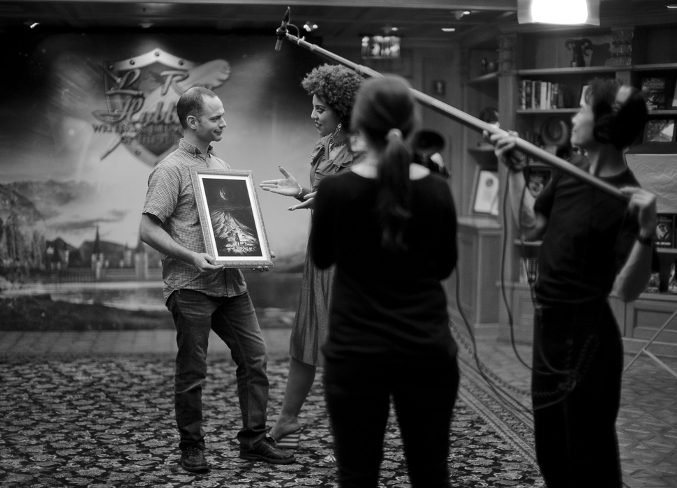 """Holding the illustration for his story, """"Moonlight One,"""" while being interviewed by Joy Villa. Photo by Thorsten Overgaard."""