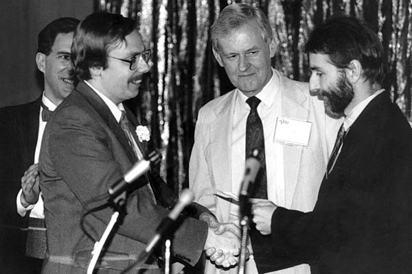 Former Gold Award winner Gary Shockley (right) and John Baker, editor of Publishers Weekly (center), present the 1990 Gold Award to James Gardner.