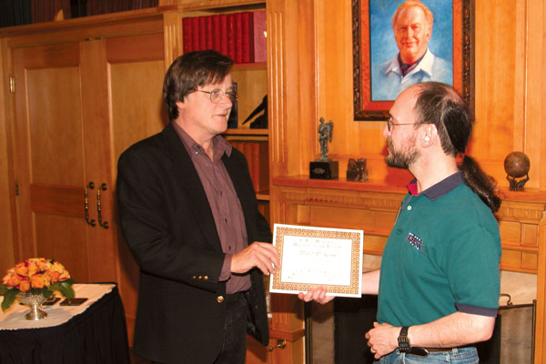 Tim Powers presents David D. Levine with his workshop completion certificate.