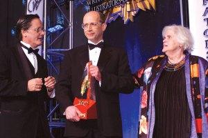 Tim Powers and Anne McCaffrey congratulate Gold Award winner John Schoffstall.