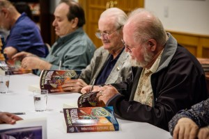 Eric Flint, Jerry Pournelle and Larry Niven pre-signing the new Writers of the Future Volume 32.