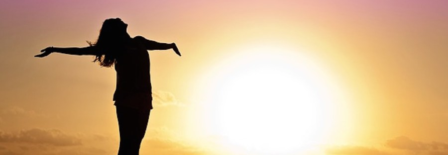 Silhouette of a woman with her arms thrown wide in joy