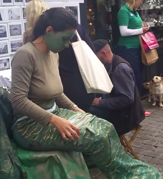Girl dressed as a Merrew in Shop Street in Galway: according to tradition they can herald a forthcoming death like a Banshee (normally a river or lake dwelling variety), or lure men to their deaths like the Siren of European mythology, and there are tales of mortals marrying merrew as well!