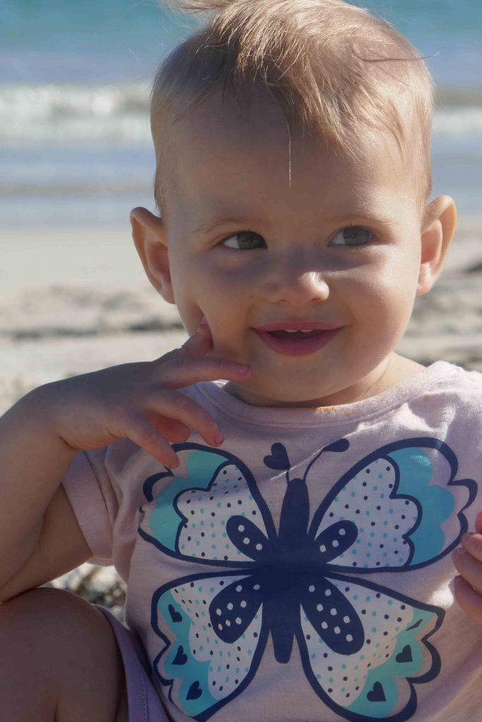 https://www.writteninwaikiki.com/10-tips-taking-better-photos-kids/ child smiling beach Waikiki Rockingham Western Australia